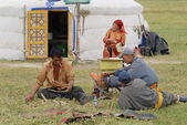 Mongolian family members fix traditional horse saddle in front of the yurt (nomadic tent) entrance circa Harhorin, Mongolia. — Stock Photo