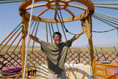 Mongolian man assembles yurt (ger or nomadic tent) in steppe circa Harhorin, Mongolia. — Stock Photo