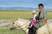 Mongolian man rides on horseback with a kid circa Harhorin, Mongolia. — Stock Photo