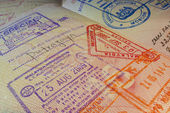 Passport page with Malaysian visa and immigration control stamps. — Photo