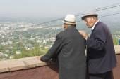 Two senior kazakh men talk and enjoy the view to Almaty city in Almaty, Kazakhstan. — Stock Photo
