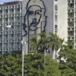 People pass iconic Ministry of Interior Defense building at the Square of Revolution with the portrait of Che Guevara on it's facade in Havana, Cuba. — Stock Photo #62901717