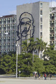 People pass iconic Ministry of Interior Defense building at the Square of Revolution with the portrait of Che Guevara on it's facade in Havana, Cuba. — Stock Photo