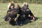 Men hold golden eagles (Aquila chrysaetos), Almaty, Kazakhstan. — Stock Photo