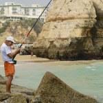 Постер, плакат: Man does fishing at Praia da Rocha beach in Portimao Portugal