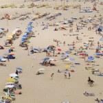 Постер, плакат: People sunbathe at Praia da Rocha beach in Portimao Portugal