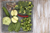 Set of vegetables on white painted plate and wooden background: kohlrabi, cucumber, apple, pepper, brussels sprouts, pea pods, broccoli. — Stock Photo