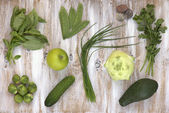 Set of green vegetables on white painted wooden background: kohlrabi, avocado, brussels sprouts, apple, cucumber, green onion, pea pods, parsley, basil. — Stock Photo