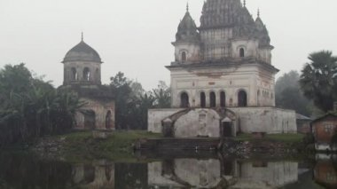 Exterior of the Shiva temple reflecting in the Shiv Sagar lake on a foggy morning in Puthia, Bangladesh. — Wideo stockowe