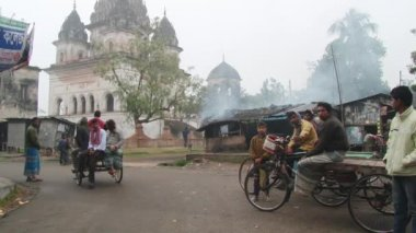 People ride bicycles by the street on a cold foggy morning in Puthia, Bangladesh. — Stock Video