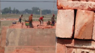 Stack of bricks with people working at the brick factory at the background in Dhaka, Bangladesh. — Стоковое видео