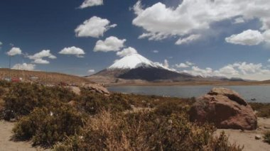 View to the Chungara lake and Parinacota volcano with trucks waiting in line for border control in Lauca Natioanl Park, Chile. — Stock Video