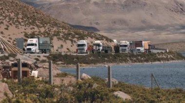 Samochody ciężarowe czekać w kolejce na przejście graniczne na granicy Boliwii i Chile w Putre, Chile. — Wideo stockowe