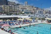 People swim and sunbathe at the open air public swimming pool in Monaco. — Stock Photo
