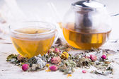 Glass teapot and cup of hot herbal tea with dry roses — 图库照片