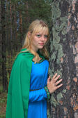 The girl in the green raincoat, nestled on a pine — Stock Photo