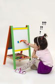 Musingly girl glues magnetic letters on white board — Stock Photo