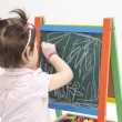 Little girl scratches with chalk on blackboard — Stock Photo #68910609