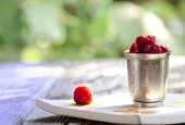 Raspberries in a cup and on a white flowered plate — Stock Photo