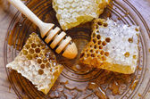 Honeycomb with honey dipper on vintage wooden plate — Stock Photo