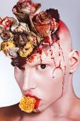 Freak boy with bloody roses — Stock Photo