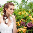 The bride in a lush garden surrounded by flowers — Stock Photo #61168875