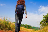 Young woman with backpack is walking on a dusty country road — Stock Photo