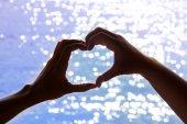 Älska formen hand siluett i bakgrunden av havet — Stockfoto