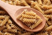 Raw brown pasta on a wooden spoon — Stock Photo