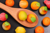 Marzipan fruit shapes in a wooden spoon — Stock Photo