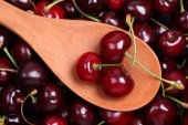 Sweet cherries in a wooden spoon — Stock Photo