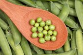 Green peas in a wooden spoon — Stock Photo