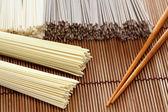 Japanese noodles with chopsticks on bamboo napkin — Stock Photo