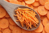 Grated carrots in a wooden spoon — Stock fotografie