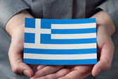 Greek flag in palms — Stock Photo