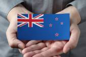 New Zealand flag in palms — Stock Photo