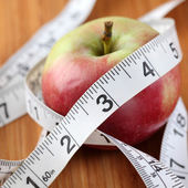 Apple wrapped in a tape measure — Stock Photo