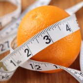 Orange wrapped in a tape measure — Stock Photo
