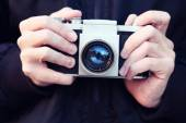 Old film camera in the hands — Stock Photo