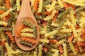 Raw colorful fusilli pasta in a wooden spoon — Stock Photo