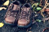 Pair of toddler boots lying on the ground — Stock Photo