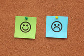 Paper with happy and sad faces on corkboard — Stock Photo