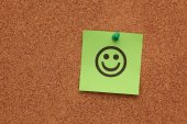 Green paper with smiling face on corkboard — Stock Photo