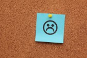 Blue paper with sad face on corkboard — Stock Photo