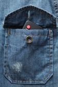 Remote control in the denim shirt pocket — Stock Photo