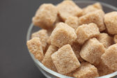 Brown cane sugar in a glass bowl — Stock Photo