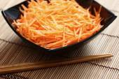 Grated carrots in bowl with chopsticks — Stock Photo