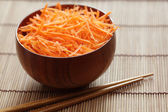 Grated carrots in bowl with chopsticks — Stock fotografie