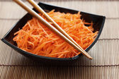 Grated carrots in bowl with chopsticks — Foto de Stock