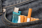 Cigarettes and lighter in pocket of jeans — Stock Photo